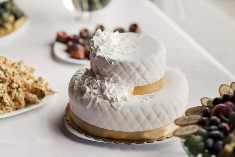 White wedding cake. Two tier white wedding cake with sugar flowers on top royalty free stock photos
