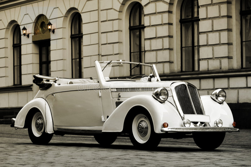 White wedding car. Beautiful retro, cream wedding cabriolet, made in 1938 year by Steyr / model 120. Photo was stylized to aged look & feel royalty free stock photo