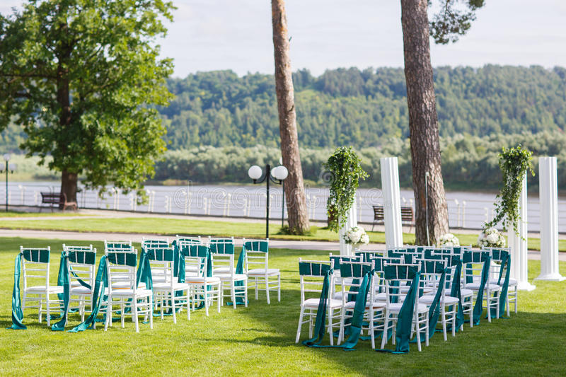 White wedding chairs with green and emerald ribbon outdoors. White wedding chairs with green ribbon outdoors stock image