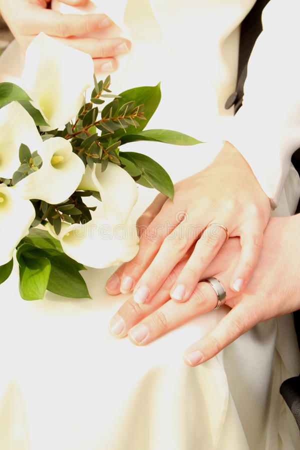 White wedding couple with flowers and hands. White wedding flowers, resting on a brides white dress stock image