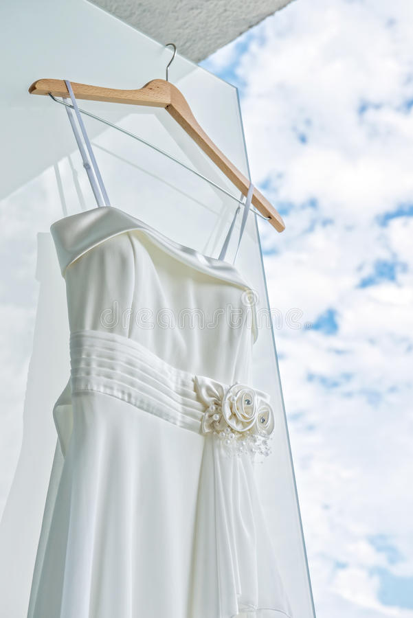 White wedding dress on front of light wall royalty free stock photos
