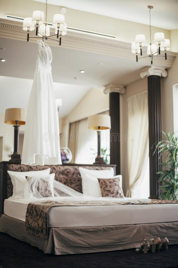 White wedding dress near the bed stock images