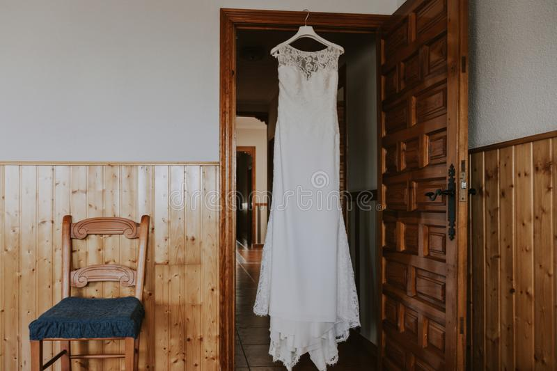 A white wedding dress hanging in a rustic house stock photo