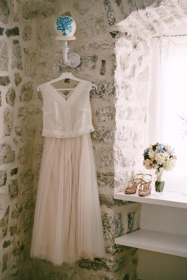 Free White Wedding Dress On A Hanger On A Wall Lamp By The Window With Sandals And A Bridal Bouquet On The Windowsill. Royalty Free Stock Photos - 197365328