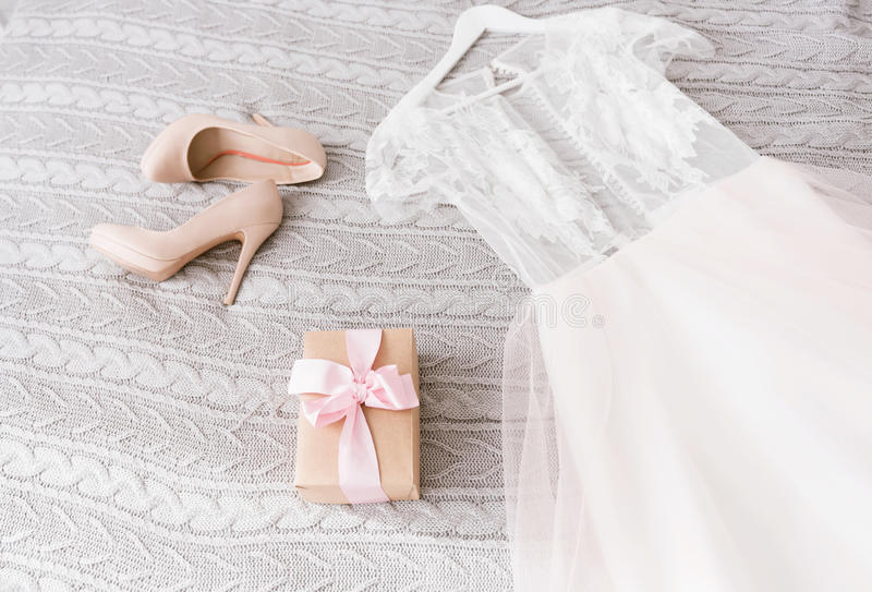 Download White Wedding Dress And Shoes Lying On The Bed Stock Photo