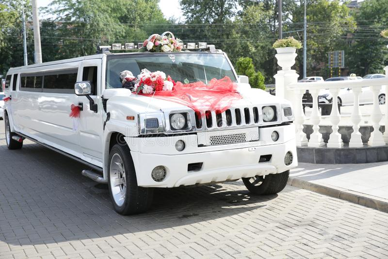 White wedding limousine decorated with red ribbons, wedding rings and flowers. Wedding concept. royalty free stock photo