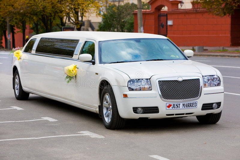 White wedding limousine on the road stock images