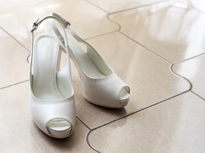 White wedding shoes. Beautiful white wedding shoes on the floor royalty free stock photos