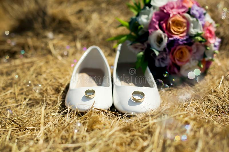 White wedding shoes and bouqet of flowers on the hay. White wedding shoes with golden rings and bouqet of color roses on the hay stock photo