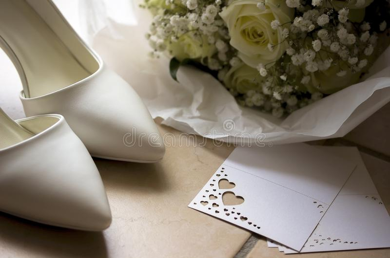 White wedding shoes with bouquet and card. White wedding shoes with bouquet and card stock photography