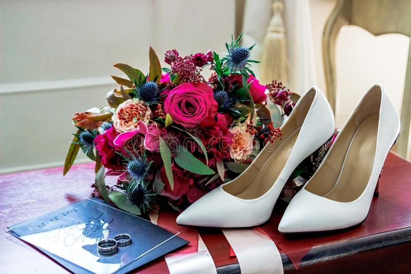 White wedding shoes bride, wedding rings and bouquet royalty free stock photos