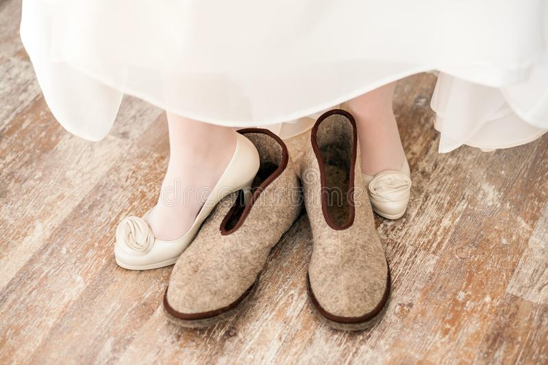 White wedding shoes on bride. With felted slippers on the background of parquet floor stock image