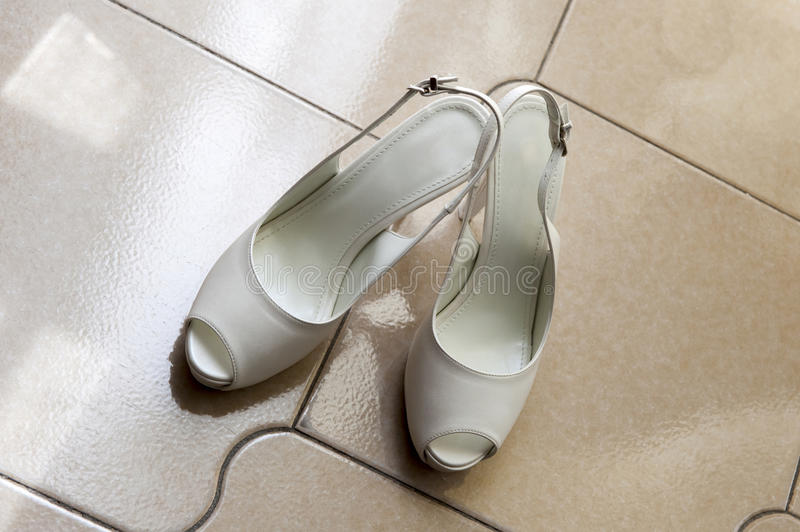 White wedding shoes. On the floor stock photos