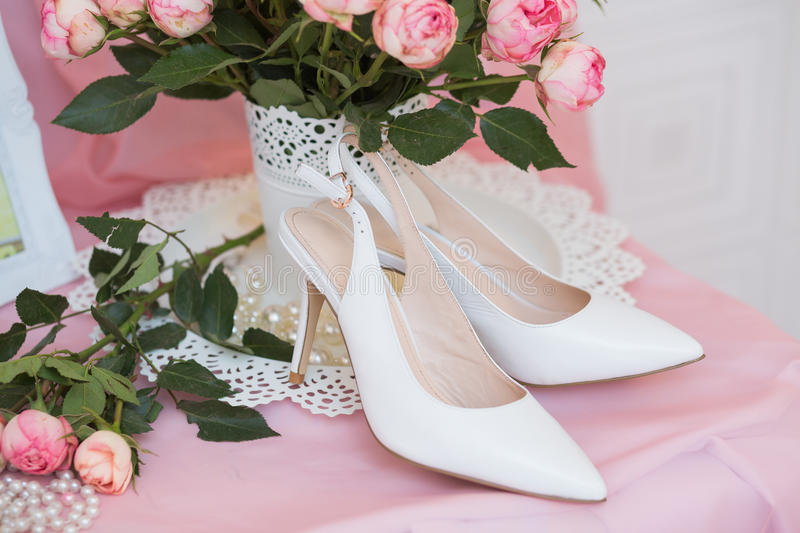 White Wedding shoes. And pink little roses stock photo