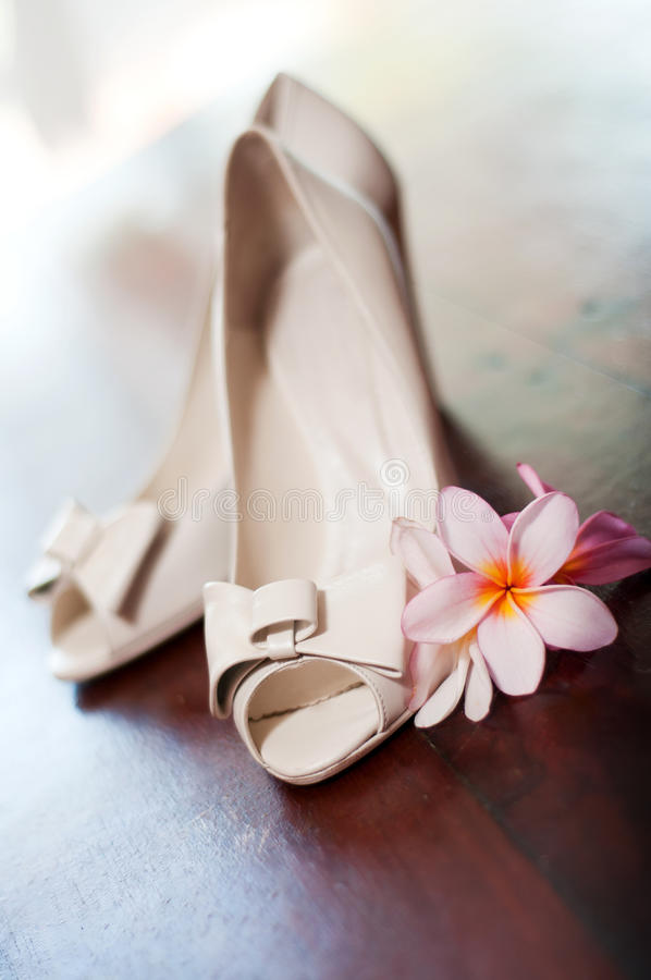 White wedding shoes with tropical flowers stock photo