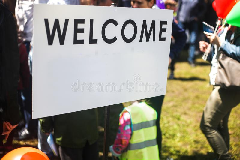 White Welcome sign in the street. Blurred people visiting an event in the city royalty free stock image