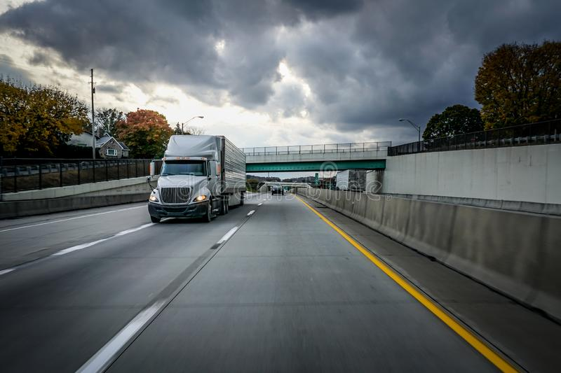 White 18 wheeler semi-truck on highway with storm clouds in the sky stock image