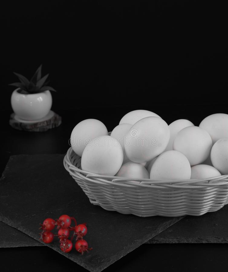 White wicker basket with easter eggs on a black background. Nearby are several red and blue berries. Monochrome photo. Space for royalty free stock image