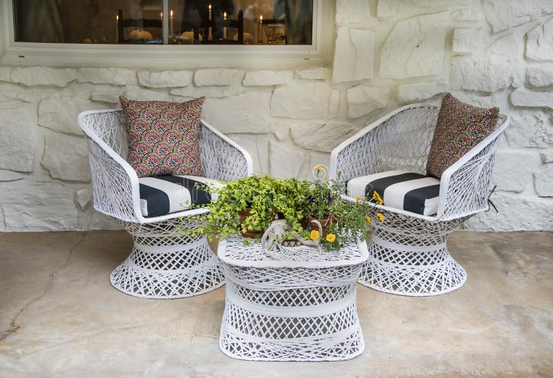 White wicker chairs and table outside on porch with Autumn flower arrangement with deer horns all against white painted stone wall. With table and candles royalty free stock images