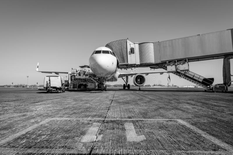 White wide body passenger aircraft with a boarding gate at the airport apron. Black and white. Airplane travel.  royalty free stock photo