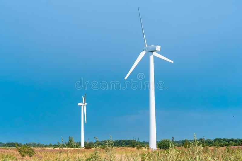 White wind power plants, two wind turbines in the field stock image