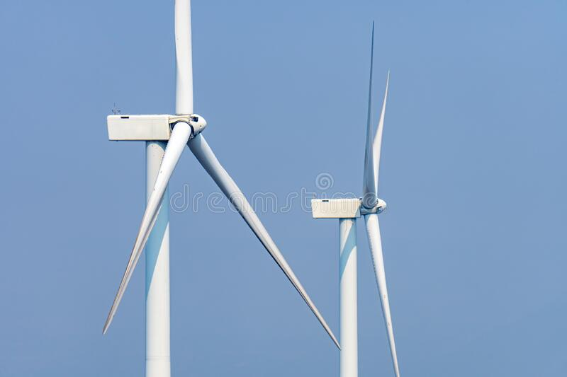 White wind power turbines or windmill generators farm for producing electricity with renewable energy. It is the way to save royalty free stock photo