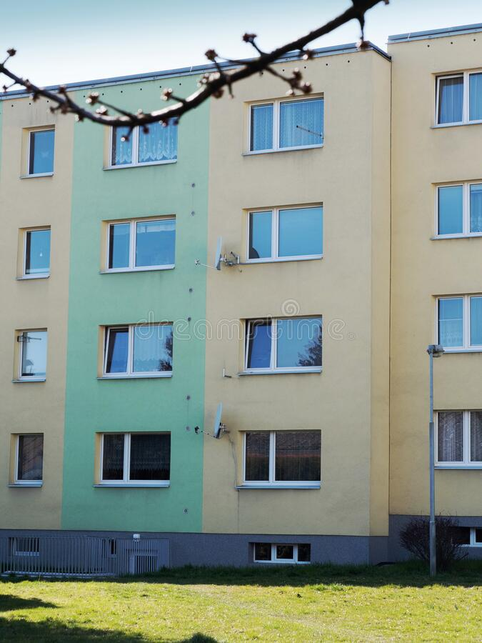 White window on a brown concrete wall of a building. White window on a blude concrete wall of low costs flats building stock image