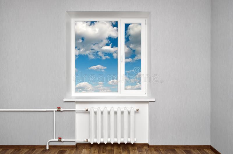 White window in empty room with heating and gray walls. Beautiful view from the window of the home stock photos