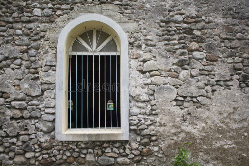 White window in old grey stone wall. Old medieval architecture. royalty free stock photo