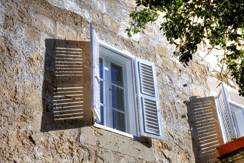 White window with open white window blinds (window shutters) in one of the old streets in Mdina, historic Malta capital.  royalty free stock image