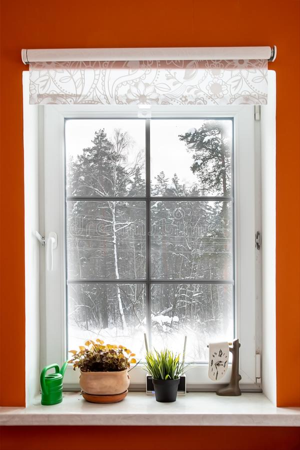 White window in orange room from which the view of the winter forest. Window to snow forest. The windows were frozen and covered stock images