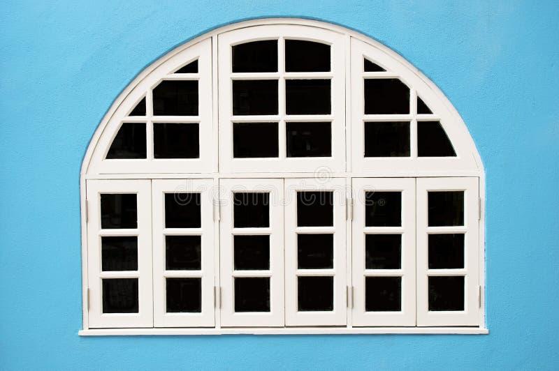 White windows. In the blue wall white Windows royalty free stock photos