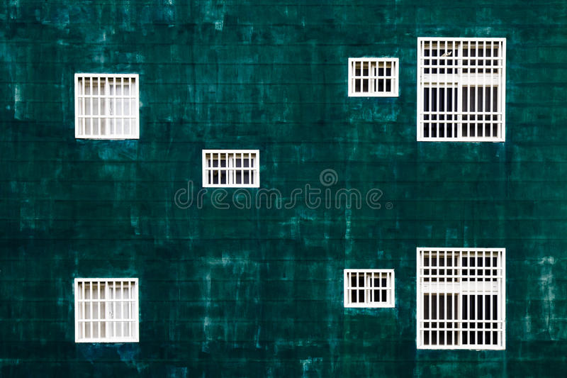 White windows against the green wall stock image