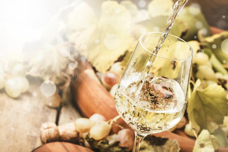 White wine being poured into a glass, vintage wood background, selective focus royalty free stock image