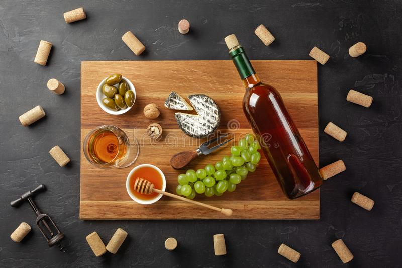 White wine bottle, cheese head, bunch of grapes, honey, nuts and wineglass on cutting board with corks and corkscrew on black stock image