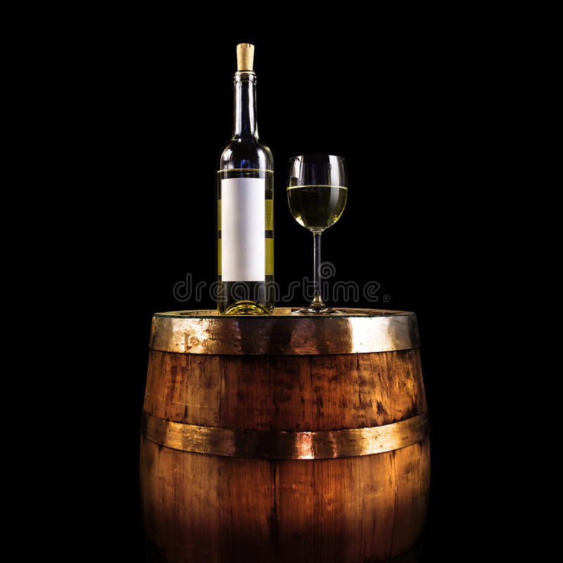 White wine bottle and glass on a wooden barrel - isolated on black. Blank white label stock images