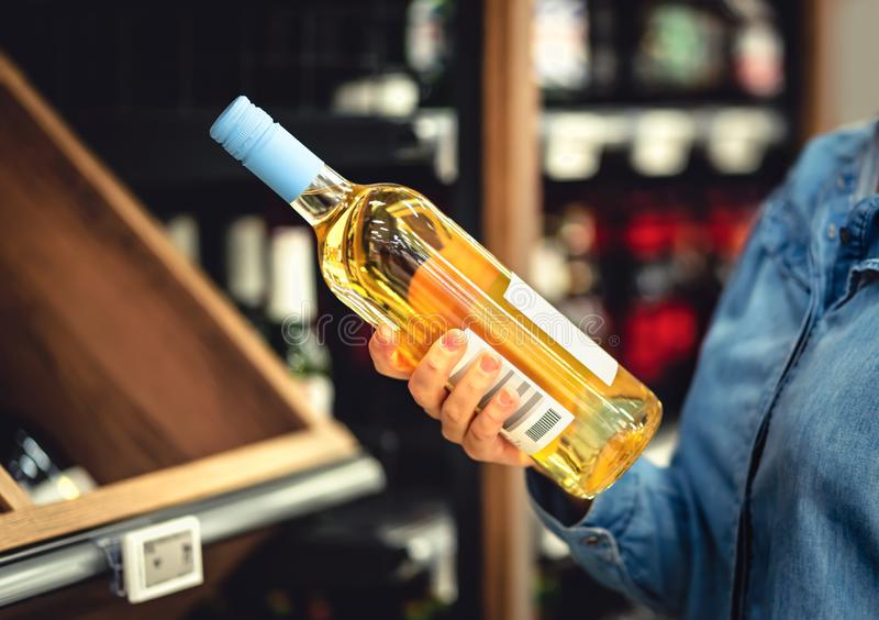 White wine bottle in hand in liquor store. Customer buying alcohol. Woman choosing the right bottle of chardonnay or riesling. stock photo