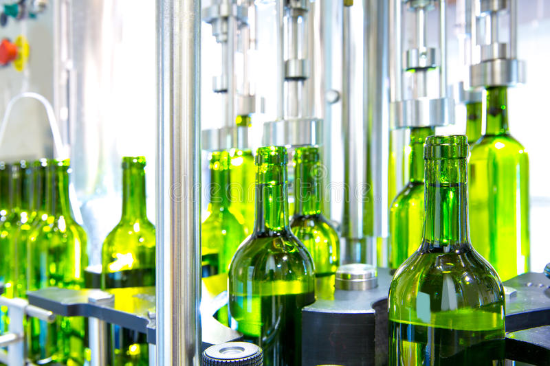 White wine in bottling machine at winery stock images