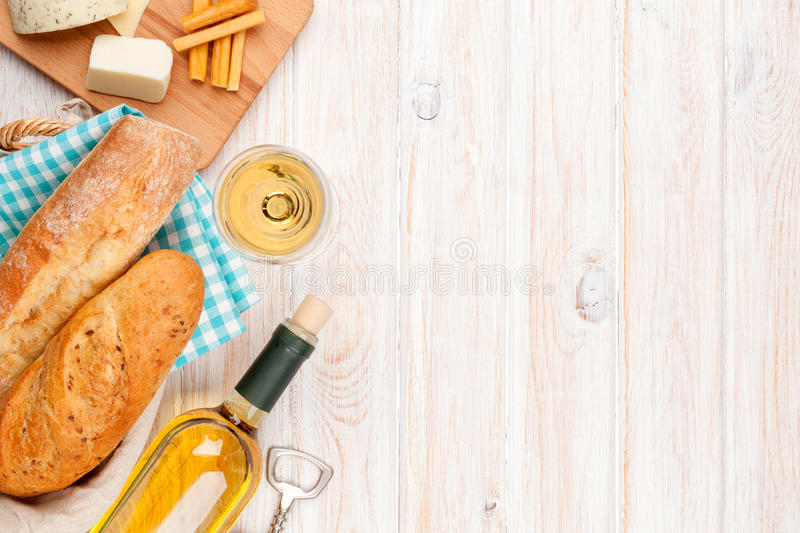 White wine, cheese and bread on white wooden table background. Top view with copy space stock photos