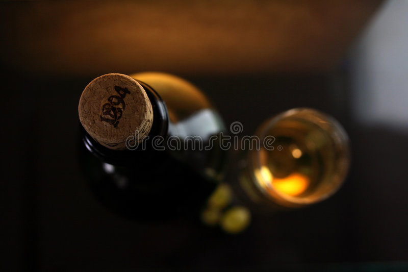 White wine glass and bottle stock photo