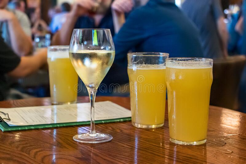 A white wine glass next to beer glasses on a wooden table at a bar in Brisbane, Australia.  stock photography