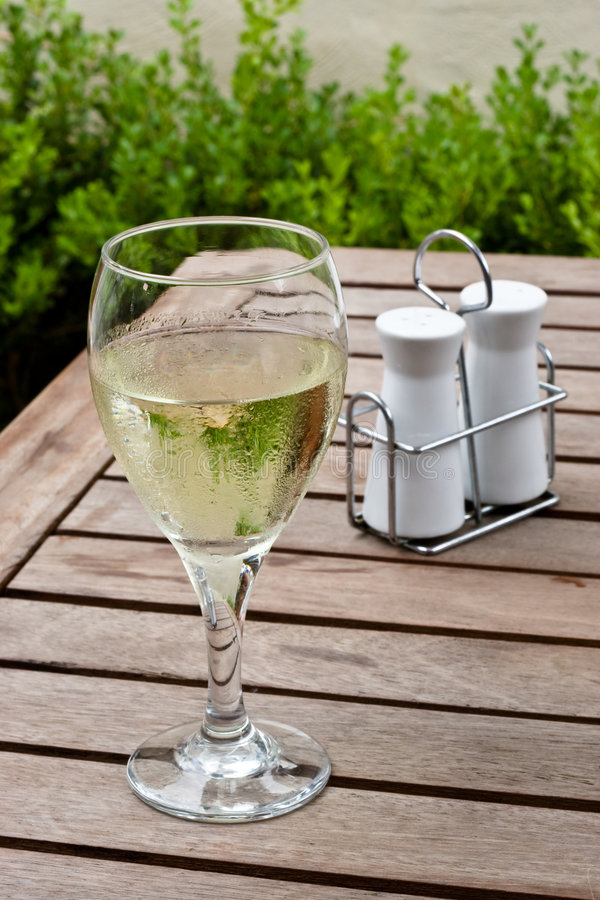 White Wine In Glass On Restaurant Table. With salt and pepper shakers in background royalty free stock photo