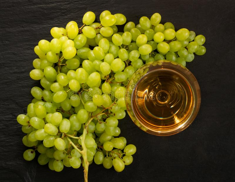 White Wine Glass on Ripe Green Grapes Background in Sunny Day royalty free stock photos