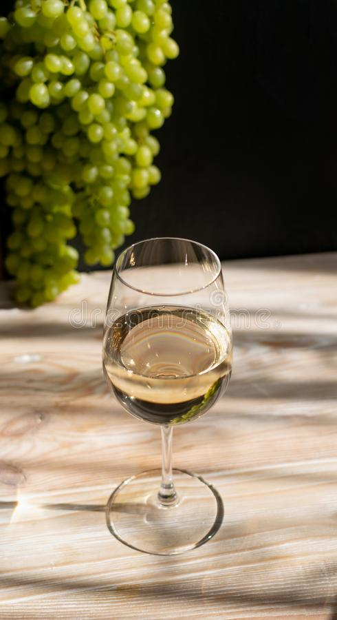 White Wine Glass on Ripe Green Grapes Background in Sunny Day royalty free stock images