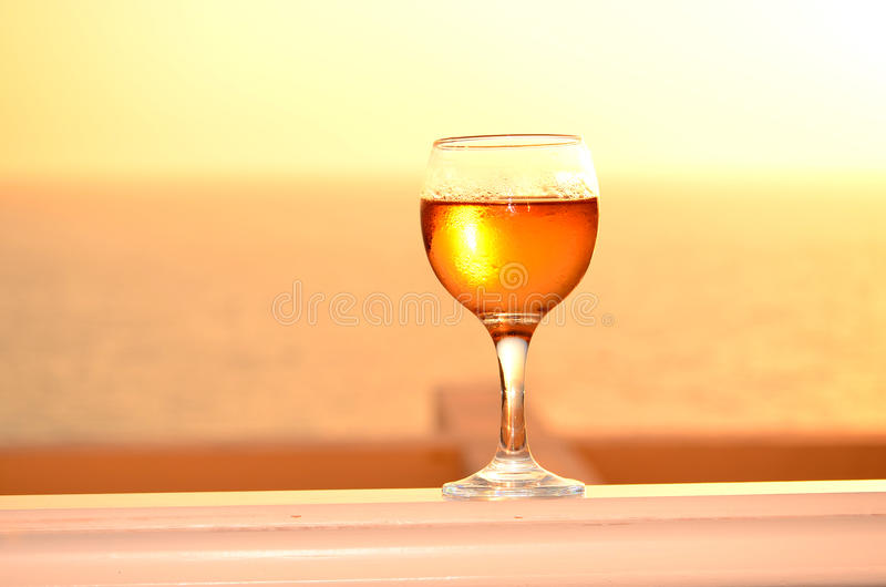 White wine glass on a sunset background royalty free stock images