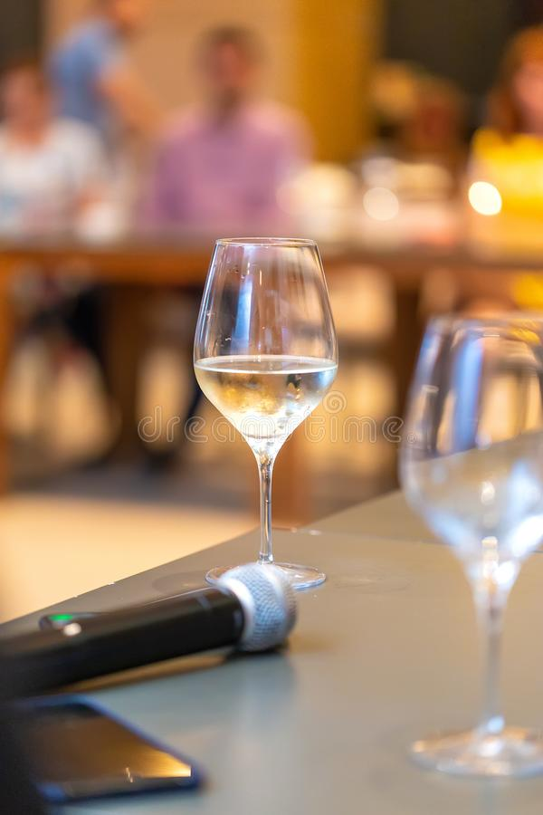 White wine glasses near the microphone on the table in a conference room. Wine tasting stock photos