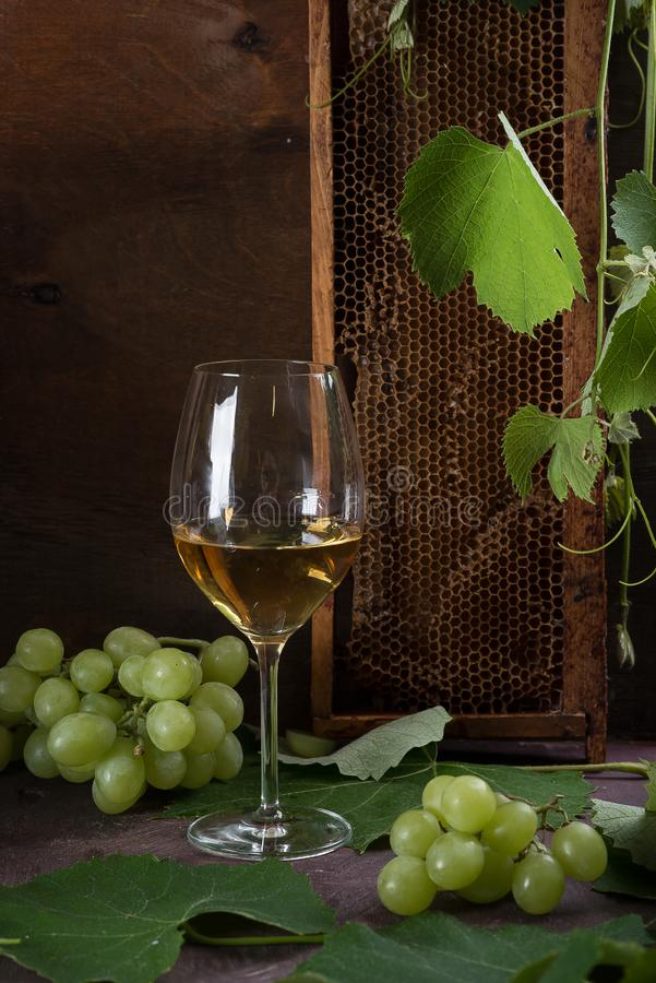 White wine in glasses. Glasses stand on a dark table next to the grape leaves and green grapes. Honeycombs royalty free stock photography