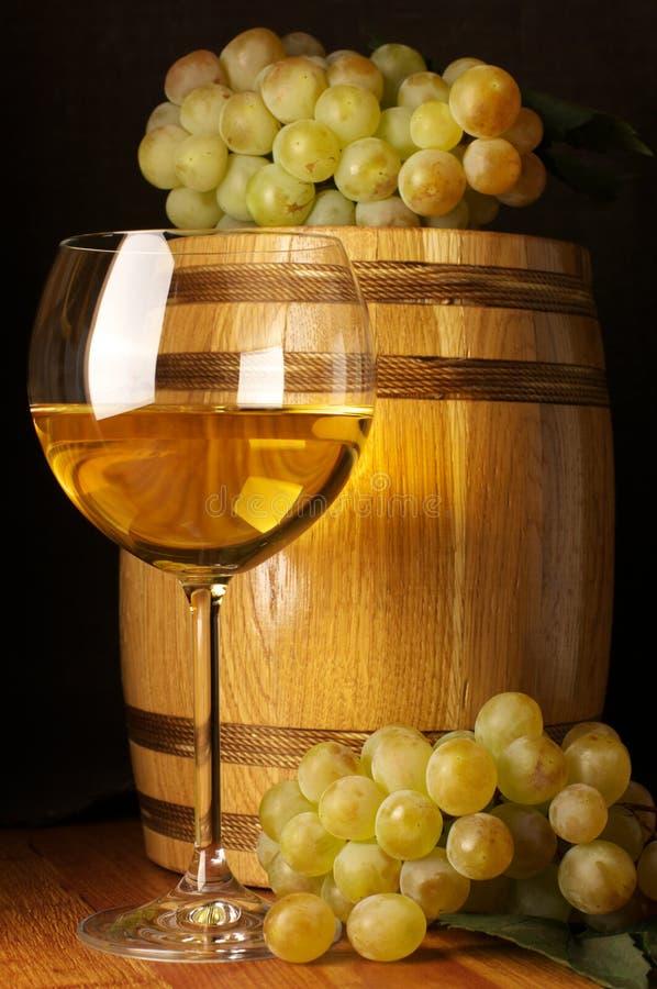White wine, grape and barrel. Glass of white wine, white grape and souvenir barrel on wooden surface stock image