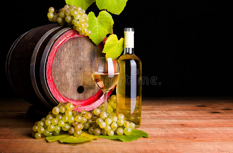 White wine and grapes in front of old barrel. White wine in bottle and glass with grape clusters and old barrel. Black background royalty free stock photography