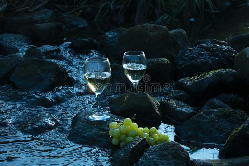 White wine and grapes Stones in the water. Colors in cool blue. White wine with a difference. Glasses with white wine and grapes on stones in a stream royalty free stock images